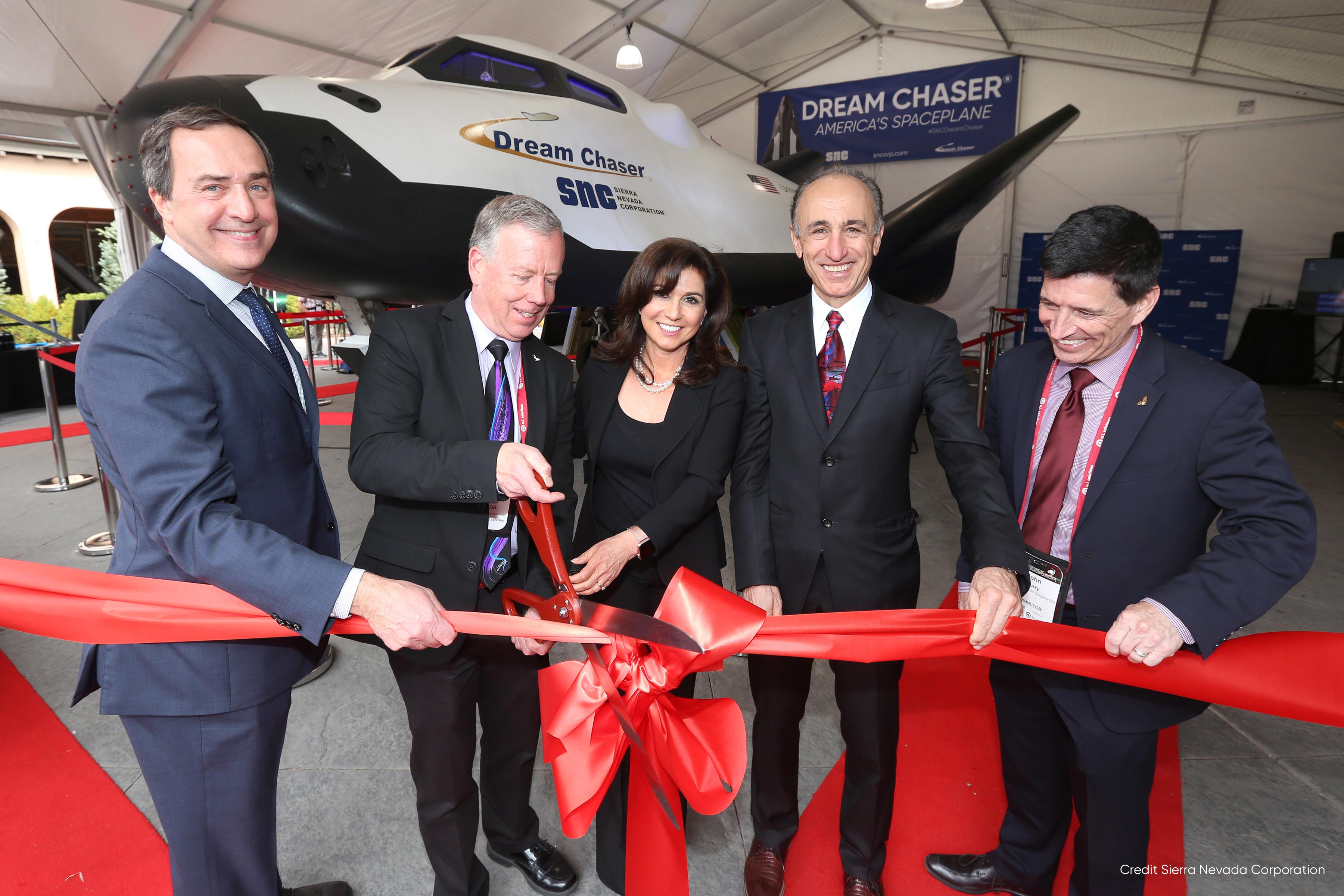 Mark Sirangelo, Steve Lindsey, Eren Ozmen, Fatih Ozmen & John Curry of Sierra Nevada Corporation cut the ribbon at the Dream Chaser exhibit at the 34th Space Symposium.