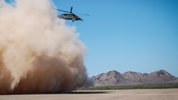 A hovering helicopter kicks up dust and dirt over a mountainous landscape