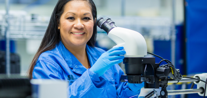Smiling SNC employee sits in front of a microscope. Learn more about benefits.