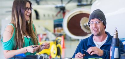 Two SNC employees collaborate in a hangar. Learn more about life at SNC.